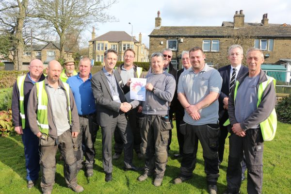 Deputy chief executive and director of strategy and integration, John Holden, presents the Estates' Gardening team with their award.