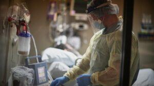A doctor adjusts a ventilator